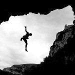 Person jumping across a rock formation